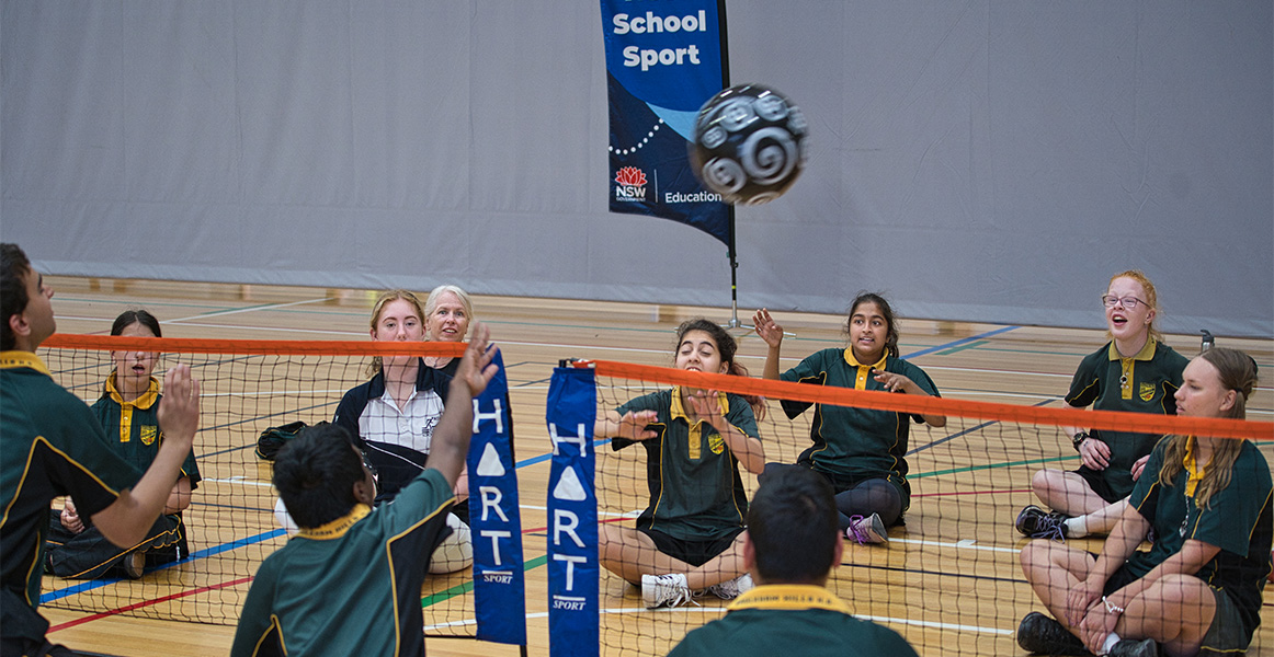 Students playing sitting volleyball